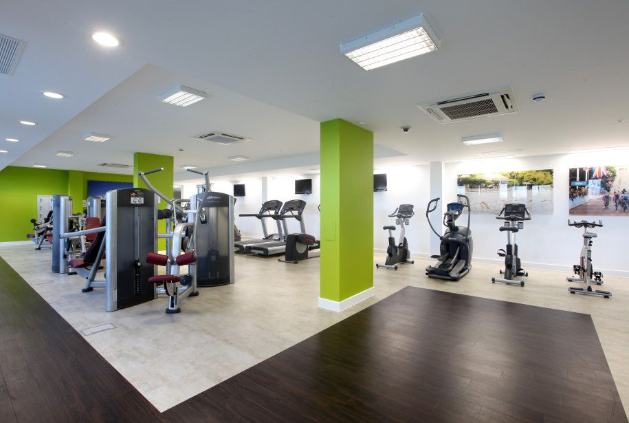 Really Cool Gym Interior Design Pictures With White Walls And Ceilings With Green Poles And