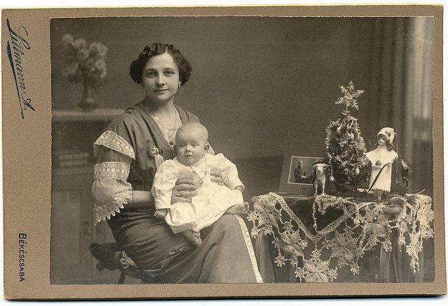 :::::::: Vintage Photograph :::::::::   Touching image of a Mother and her daughter taken next to the most precious Christmas vignette. Which includes a portrait of the husband and father who looks to be dressed in a uniform.  I imagine the photograph was taken to be sent to him while he was away in the service.  It's worth it to click on the link and enjoy close up details of the photograph.