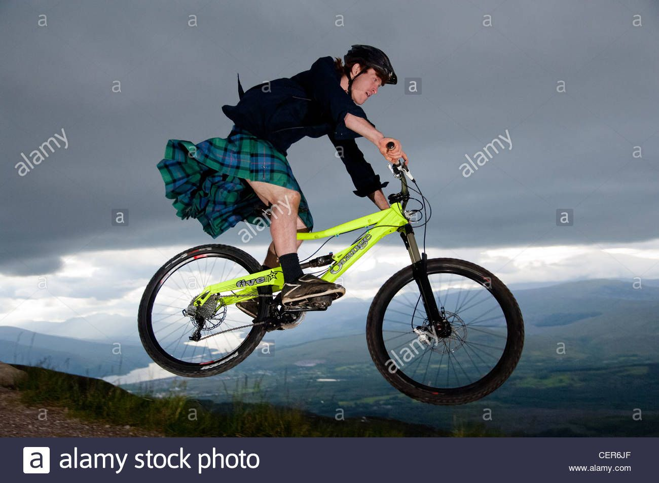 Young Man In Kilt Jumping On His Mountain Bike On The Downhill