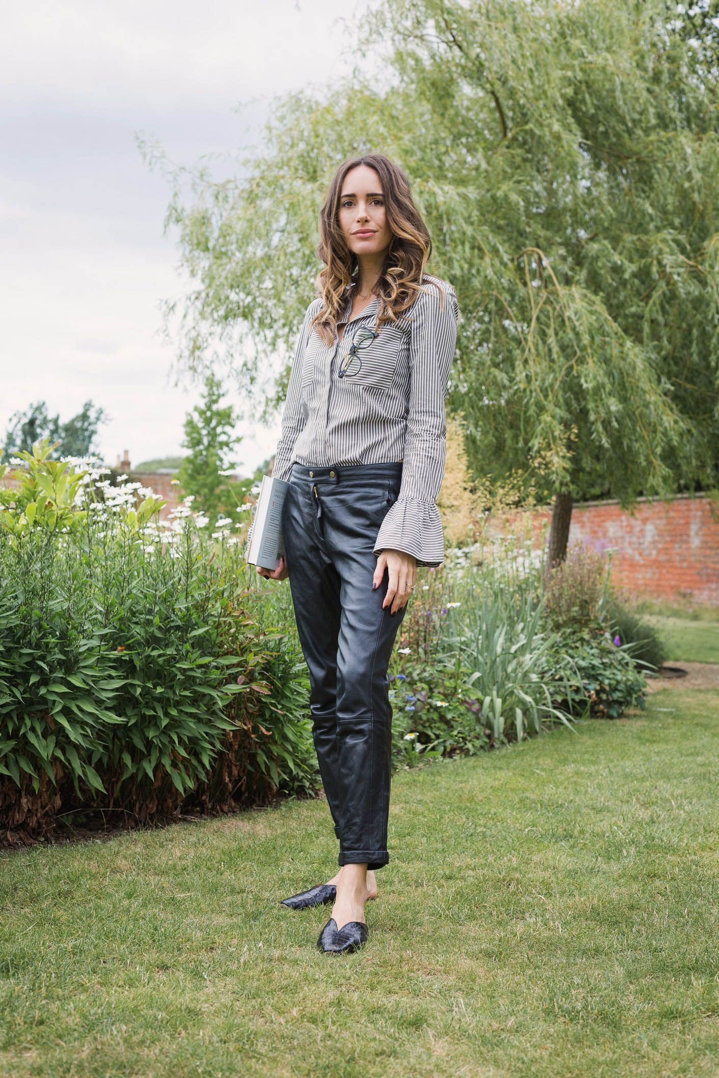 86298e26c37e5 Louise Roe showcases a chic work outfit featuring leather pants and a  striped blouse
