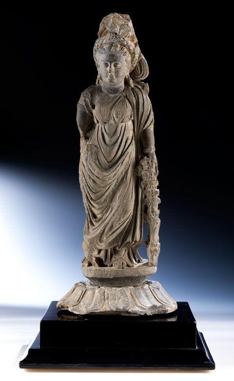 """Steinfigur einer """"Tyche"""" der Gandhara-Kultur Höhe: 58,5 cm.  Rosettenlängsdurchmesser: 24 cm.  2. Jahrhundert v. Chr."""