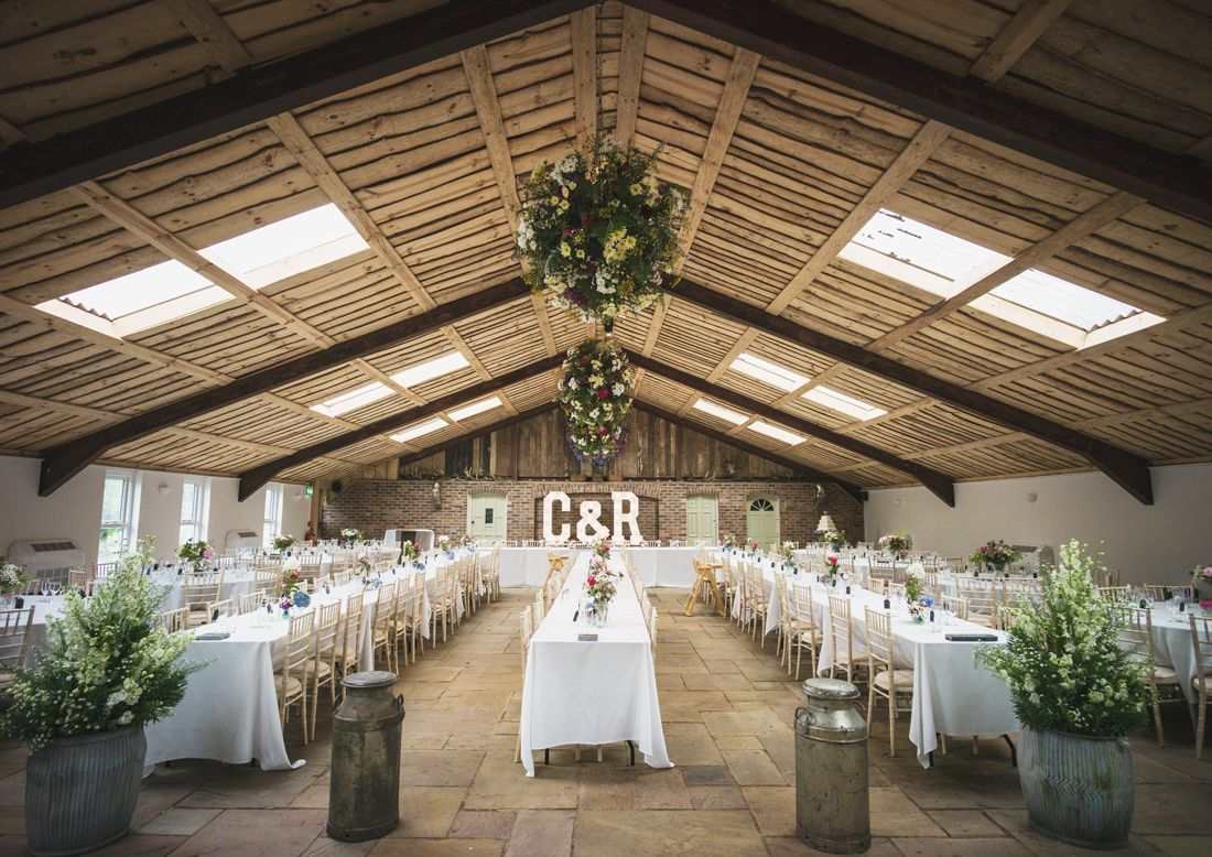 Long White Tables Stretch This Countryside Barn Location With Elegant Baskets Of Flowers Hanging From
