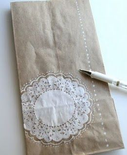 Doily glued to brown paper bag & doodling added w/ a white gel pen. Would be super cute on butcher paper!