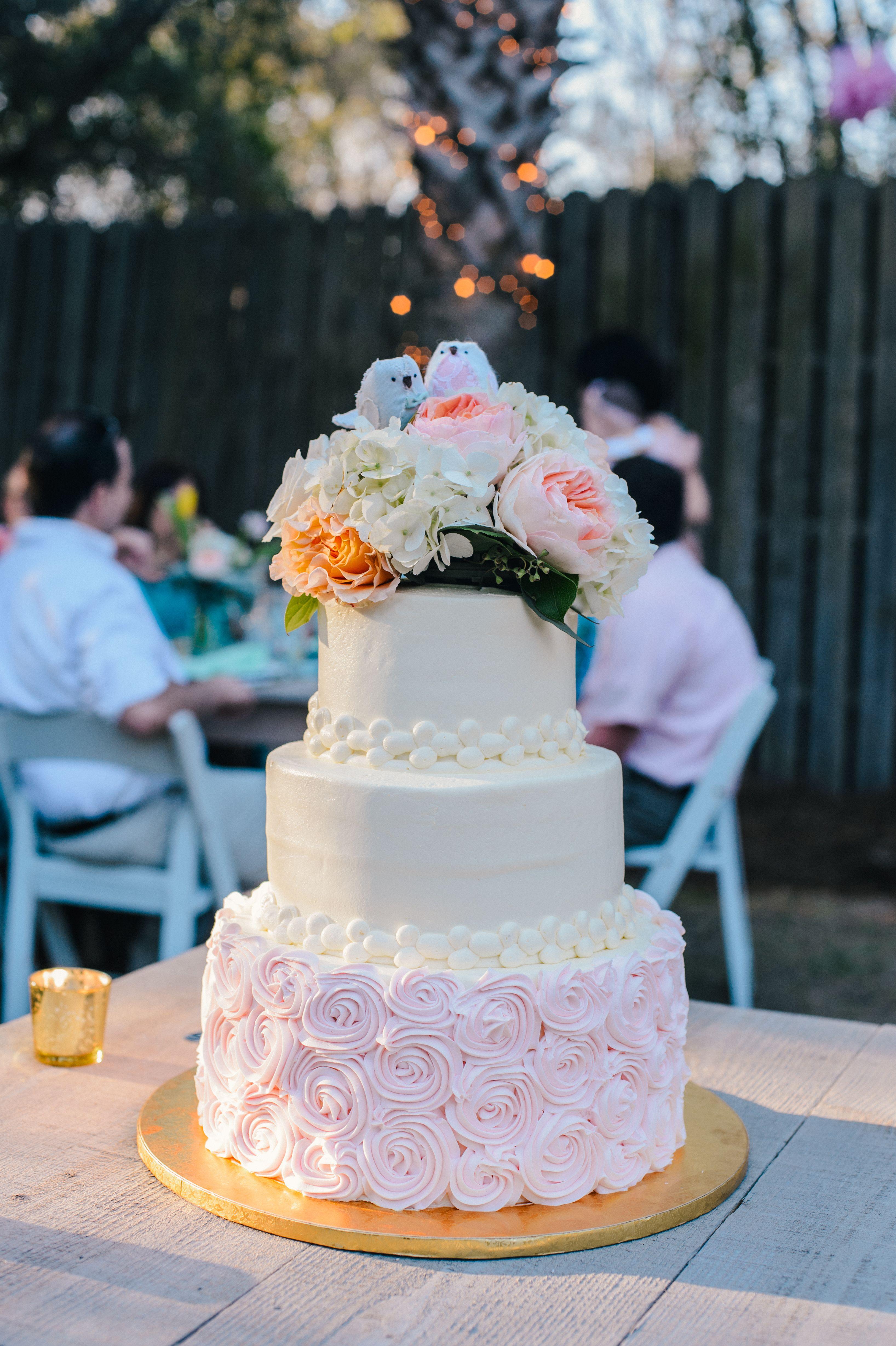 Pink rosetta wedding cake with love birds and peonies