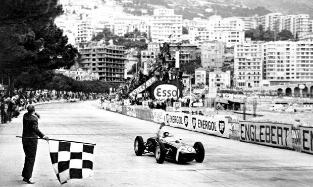Stirling Moss raises his hand in victory before taking the chequered flag at the 1961 Monaco Grand Prix.