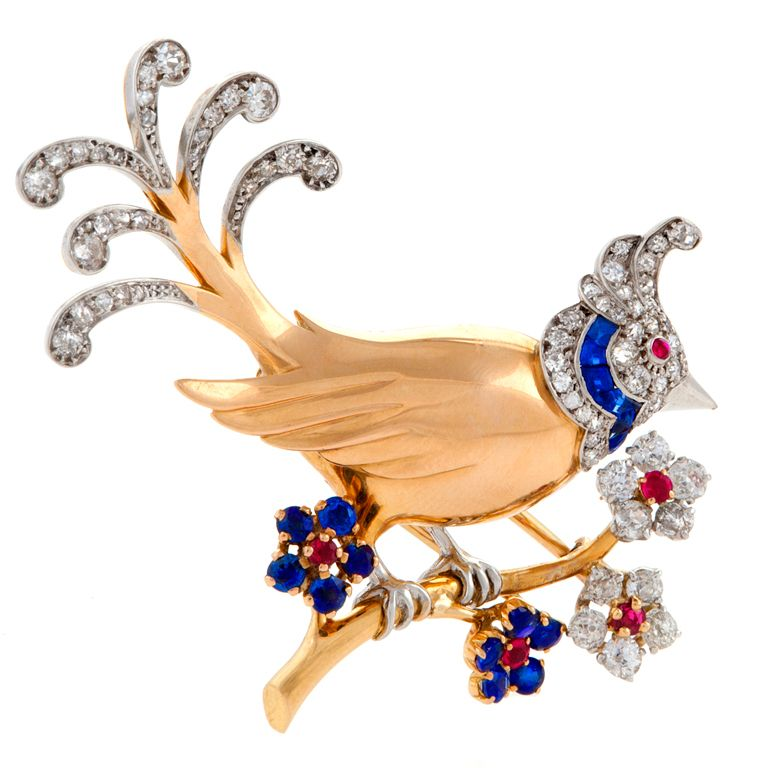 Mauboussin Mid 20th Century Gem Set Diamond Gold Stylized Bird Brooch The brooch has 62 round-cut diamonds with an approximate total weight of 1.40 carats, 16 blue sapphires with an approximate total weight of .75 carats and 5 rubies with an approximate total weight of .23 carats.