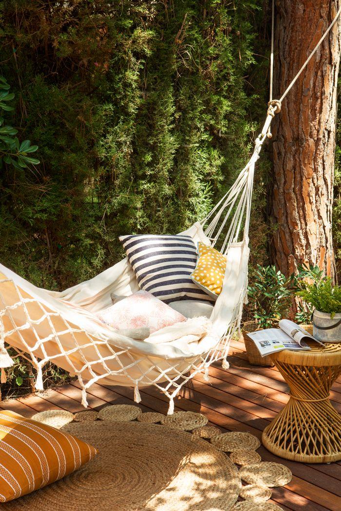 Hamaca colgada de árbol. Debajo, una alfombra de fibras, cojines y ...
