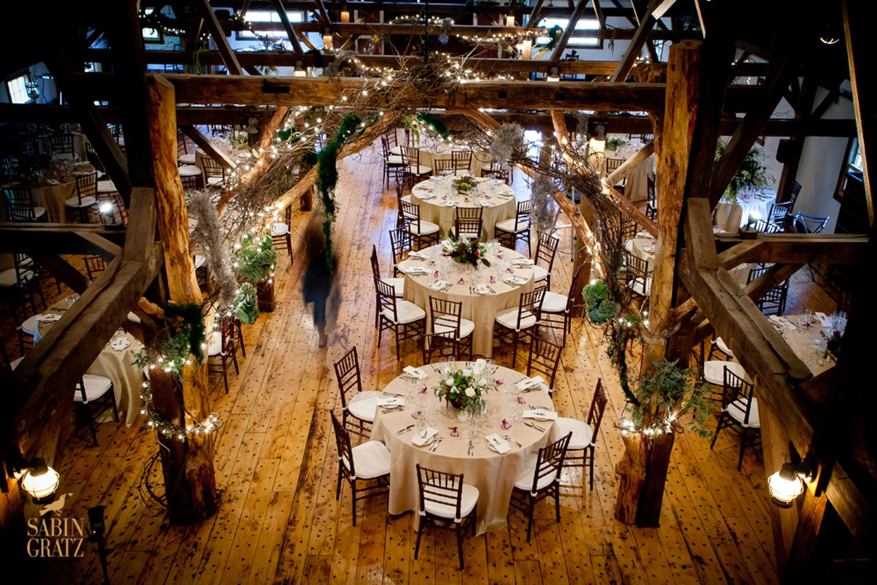 Stonewell Barn – Vermont Weddings  these chairs at least have cushions  additional greenery also, and little lights.  if you don't like white tablecloths then maybe a beige like this