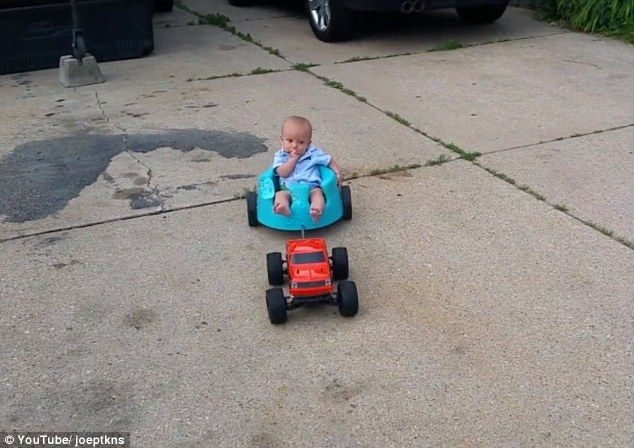 Father Attaches Remote Control Car To Baby Seat And Tows Toddler