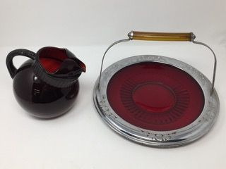 LOT INCLUDES A VINTAGE FARBERWARE CHROME SERVING PLATTER WITH RUBY RED GLASS INSERT AND APPLE JUICE BAKELITE HANDLE. LOT ALSO INCLUDES A RUBY RED GLASS PITCHER.