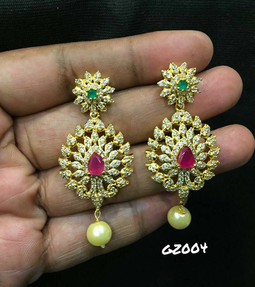 Beautiful earrings studded with white green and pink color stones ...