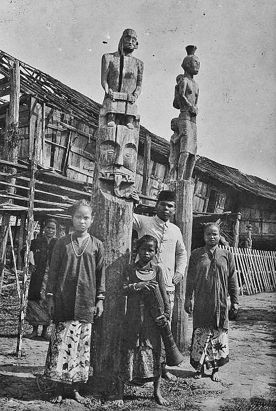 Mensen bij twee offerpalen te Melawi op Borneo. 1920