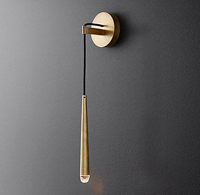 "RH Modern's Aquitaine Sconce 21"":Inspired by French minimalist lighting of the 1960s, Jonathan Browning's elegant design features a solid brass form suspended from a slender black cord. An inset LED bulb at the tip offers warm, glowing light."