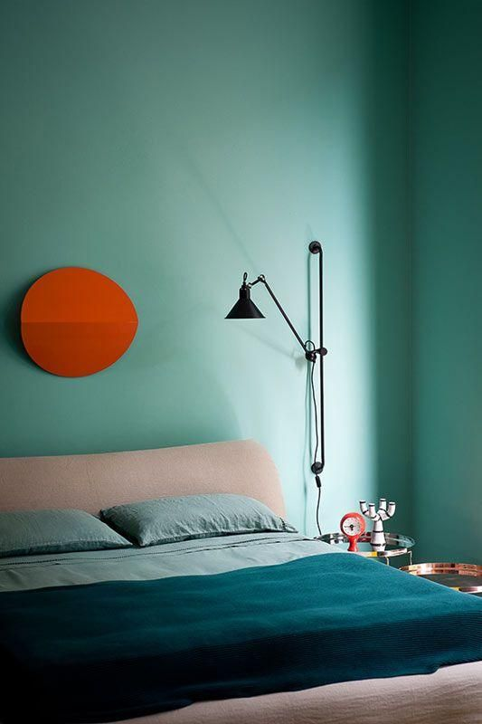 High Quality Minimalist Blue Bedroom With Black Wall Sconce And Peach And Orange Accents.