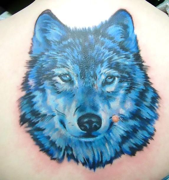 A Tattoo Of A Blue Wolf On The Man S Back Style Realistic Color Blue Tags Beautiful Cool Tattoos For Guys Lone Wolf Tattoo Wolf Face Tattoo