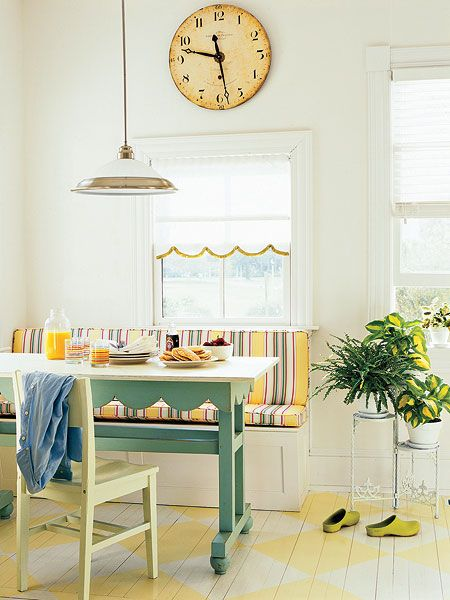 A table and built-in bench create this cheerful breakfast nook. A striped cushion ties the yellow harlequin-pattern painted floors to the green-blue finish of the breakfast table. A subtle pendant light, Roman shades, and an antique-style wall clock complete the vintage look. (Photo: Erik Johnson)
