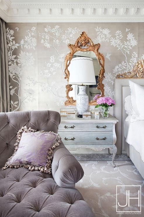 Gray and gold French bedroom features a wall clad in gold ...