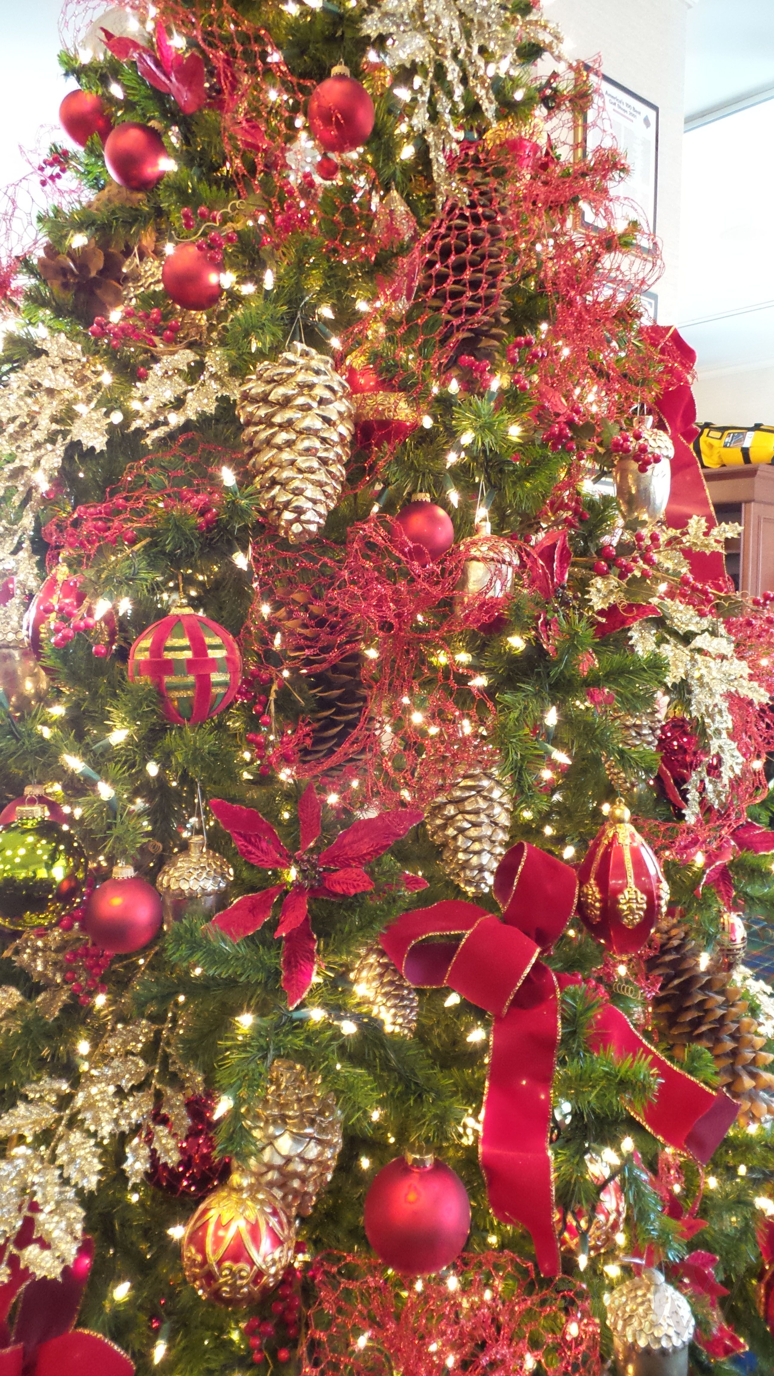 Beautiful red and gold Christmas tree with pine cone embellishments