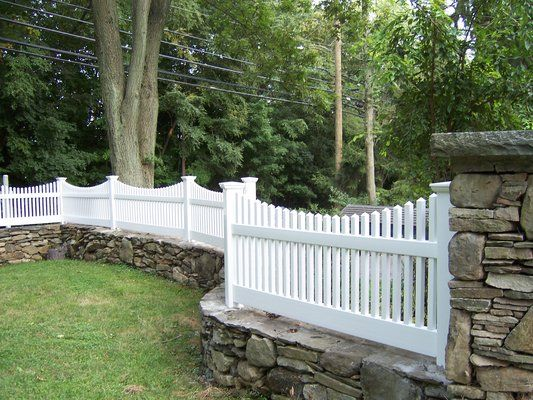 VICTORIAN FENCE Victorian picket fence set on stone wall, in