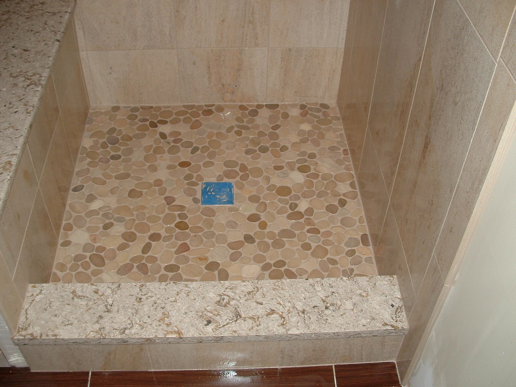 Custom Shower Base With Sliced River Stone Floor And Stone Curb.