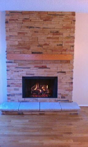 Fireplace With A Short Cultured Ledge Stone Raised Hearth