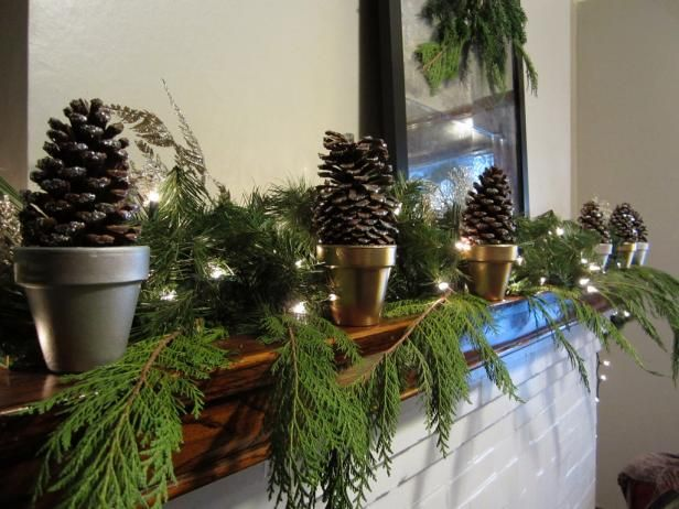 Check out this stunning winter fireplace mantel display featuring real evergreen branches and pine cones, featured on HGTV.com.