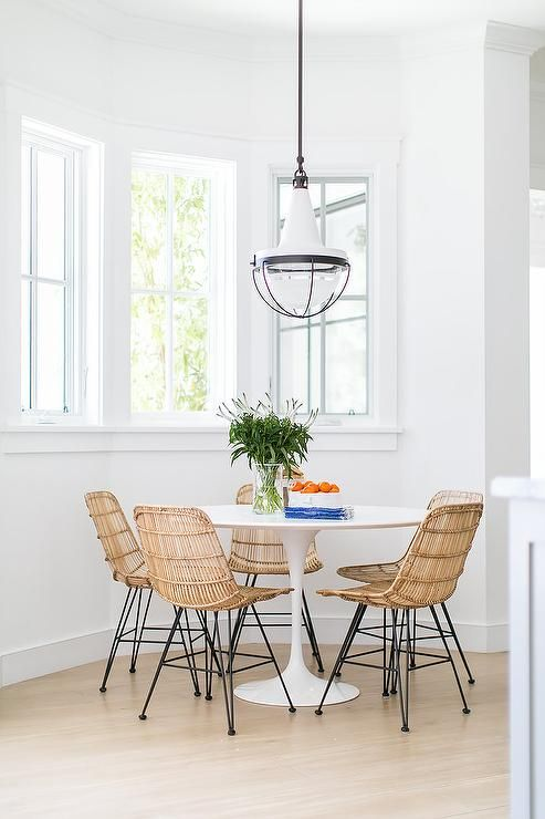 Chic Dining Nook Features A White Vintage Pendant Illuminating Round Saarinen Table Lined With Modern Wicker Chairs