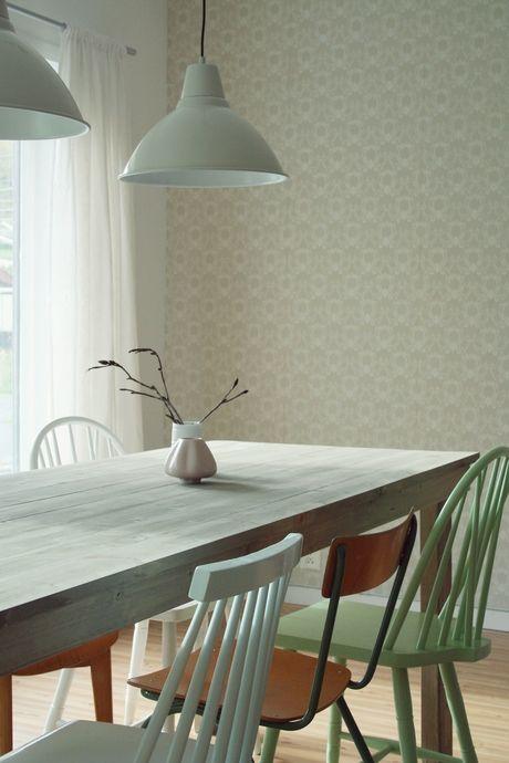 Kaksi lamppua ruokapöydän ylle, eripariset tuolit ja vihertävä tapetti.