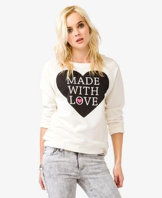 """A fleece lined pullover featuring """"Made It With Love"""" heart print graphic. Round neckline. Long raglan sleeves. Knit. Lightweight.  DETAILS:  • 23"""" approx. length from high point shoulder to hem, 40"""" chest, 38"""" waist, 29"""" sleeve length from high point shoulder  •Measured from Small  •39% cotton, 10% rayon, 51% polyester •Hand wash cold, dry flat • Imported"""