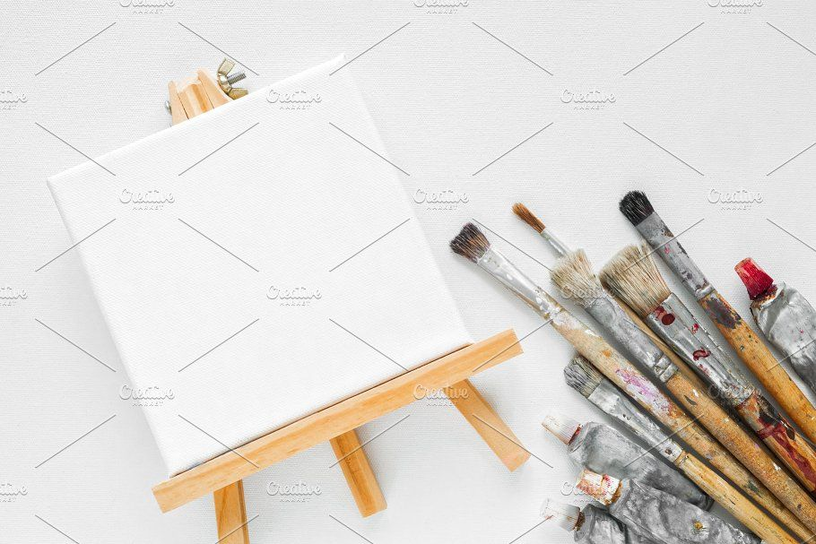 #Canvas easel paint tubes brushes  Canvas on easel paint tubes and bundle of brushes for painting on white canvas background. Top view. Flat lay. Copy space for text.