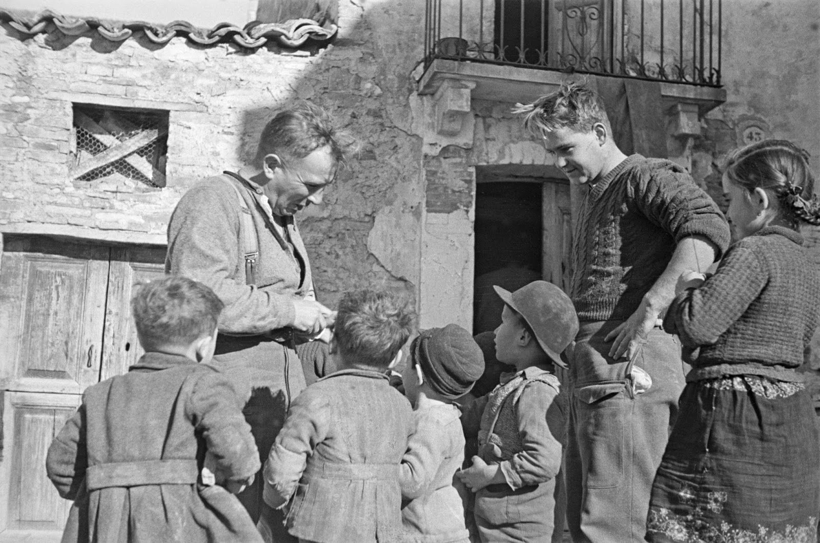 History in Photos: George Frederick Kaye. Men of 2 New Zealand Division fraternizing with children in the village where they are resting after a spell in the front line, near Orsogna, Italy, 6 January 1944