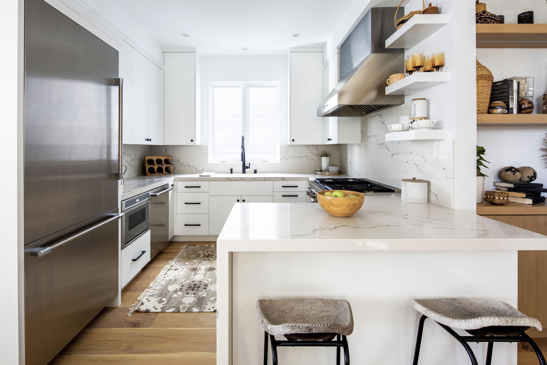Crisp, clean lines refine the functional kitchen, accented by Thermador appliances. #kitchendesign #kitchedecor #whitekitchen #modernkitchen #interiorinspiration