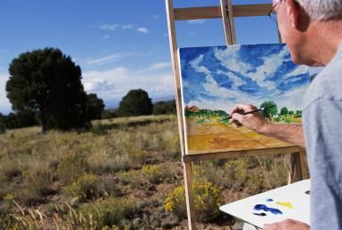 Mature man painting picture in field - Marc Romanelli/The Image Bank/Getty Images