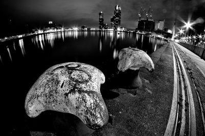 Een artistieke nachtfoto van de haven van Rotterdam. Het fisheye-effect geeft een spannende compositie. Een klein diafragma maakt van de lampen een soort sterretjes. De langere sluitertijd die je hierdoor krijgt zorgt dat het water een soort gladde spiegel wordt waar het licht op reflecteert. Al met al een spannende plaat van een spannende plek.