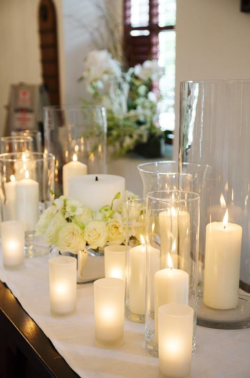 Glowing Pillar Candles In Hurricane Vases Surround A Larger Central Candle