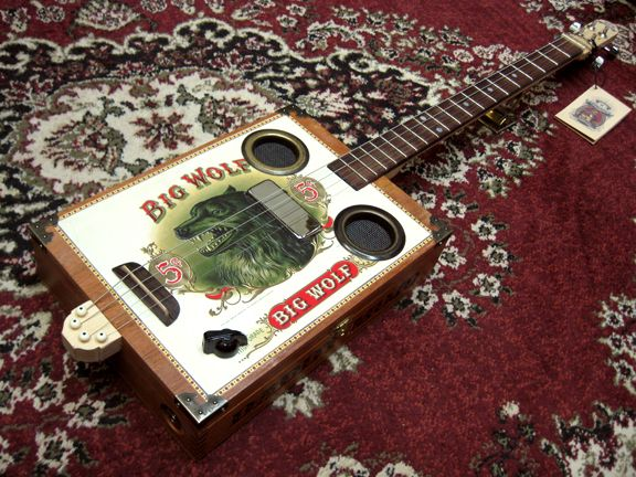 "All Daddy Mojo ""Standard Deluxe"" cigar box guitars are equipped with a maple neck, Spanish Cedar box as well as a magnetic pick-up for amplification purposes. Description from daddy-mojo.com. I searched for this on bing.com/images"