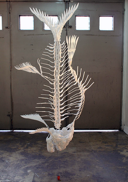 "Artist Carlos Bonil creates surprisingly realistic sculptures of skeletons, like this monumental fish skeleton called ""Fish and Pail,"" from plastic utensils that have been fused together"