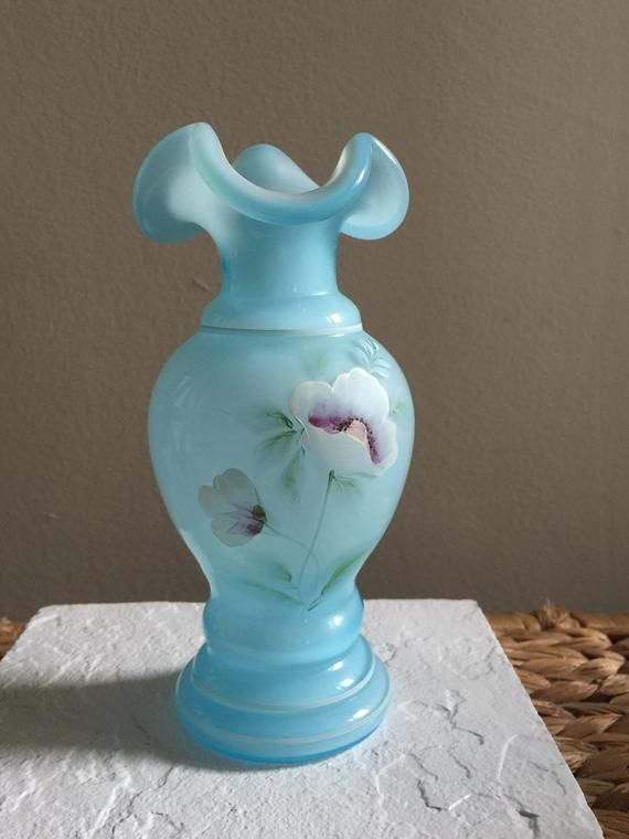 This is one of the most beautiful pieces of Fenton art glass that I have seen.  The soft, baby blue glass is hand painted beautifully by M. Coplinger.  Fenton Glass no longer produces so what is out there on the market is all there will ever be.  Vase is in excellent conditioned.  Marked with Fenton logo on the bottom.  Signed