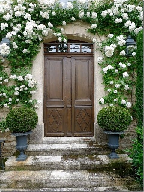 symmetrical entry with rich wooden doors, old world stonework, urns of Boxwood, and a gorgeous flowering vine to soften the lines....only question...where are the door handles?