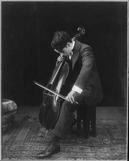 [Sir Charles Chaplin, 1889-1977, full length portrait, seated, facing right; playing cello]