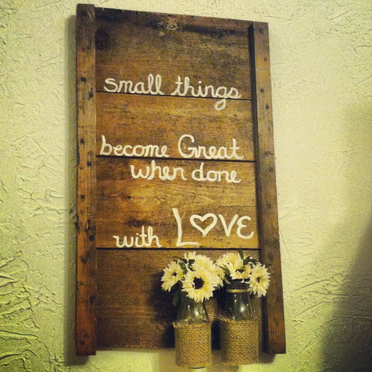 Quote painted on scrap wood with small glass bottles holding flowers