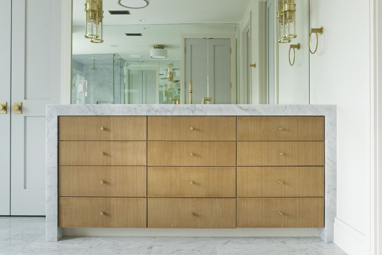 Coats Home bathroom with blond wood vanity, marble counters, brass sconce