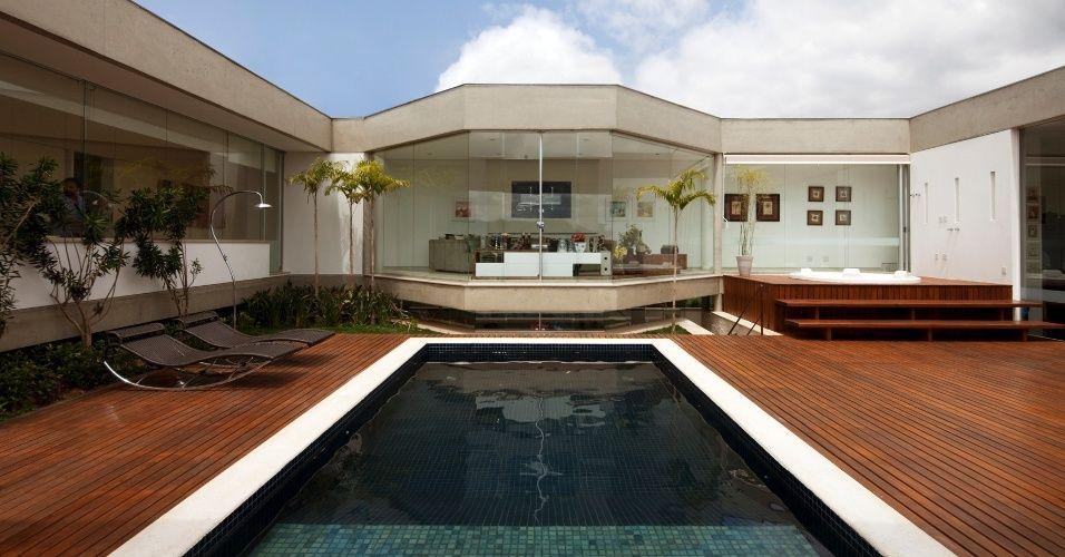 A piscina no centro do terreno com a casa envolvendo ela e desta forma podenndo ser vista de qualquer cômodo da casa