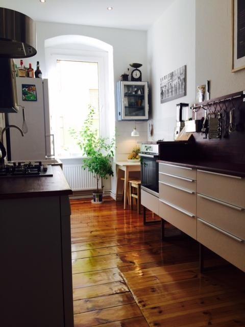 modern eingerichtete k che mit hochgl nzendem dielenboden kleiner sitzecke und hohem fenster. Black Bedroom Furniture Sets. Home Design Ideas