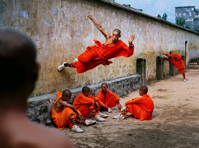 Steve McCurry, 'A young monk runs along the wall over his peers at the Shaolin…
