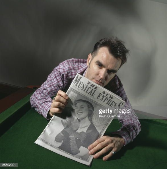 British singer Morrissey holds a 1952 copy of 'The New Musical Express' magazine to celebrate the 40th anniversary of the publication, 24th March 1992. The magazine cover features a tribute to Dame Vera Lynn.
