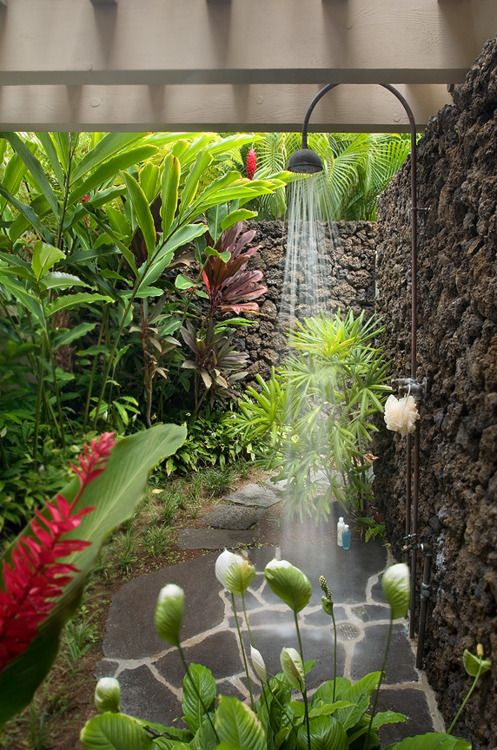 Peaceful outdoor shower with stone wall and flagstone floor, surrounded by tropical plants