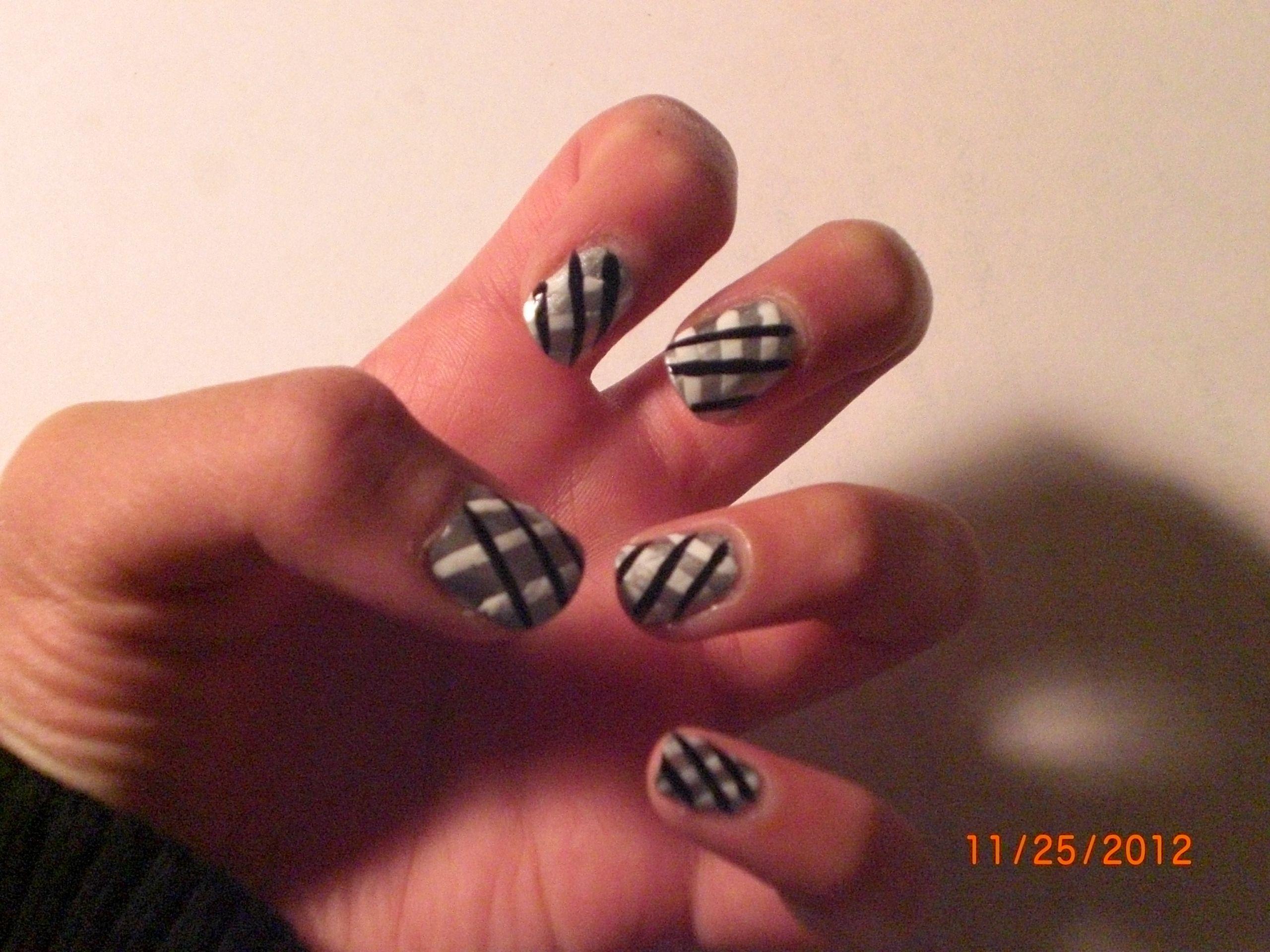 Nail art silver nail polish then add on black and white stripes