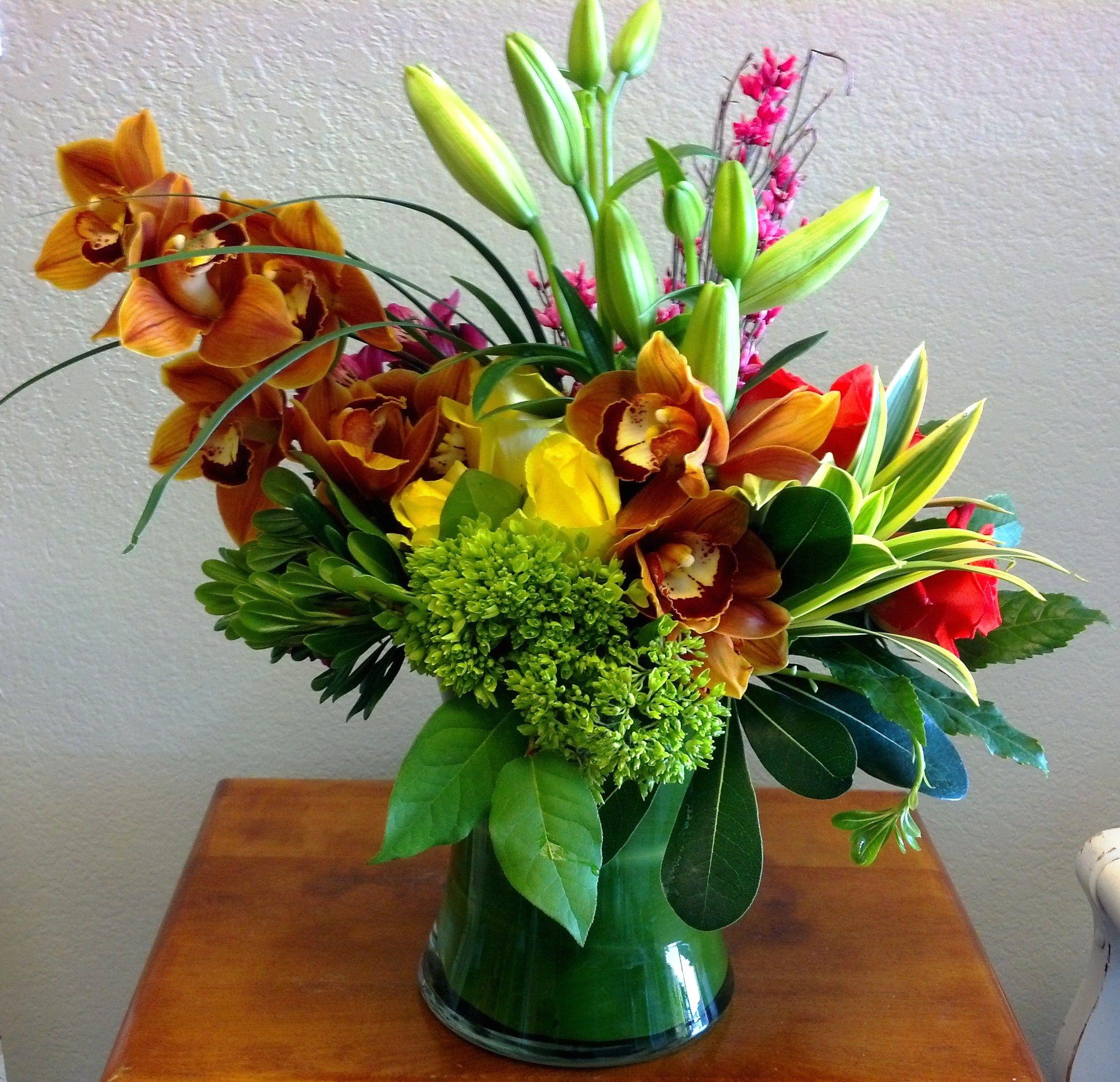 A bright, tropical flower arrangement. roses orchids