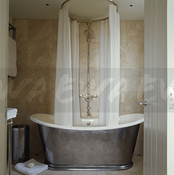 Image: White curtains on circular shower rail above grey metal ...